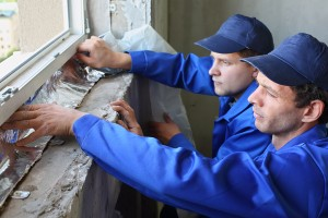 Two men in working clothes places the foiled insulation on the w